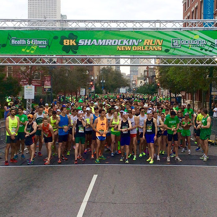 Runners Under Event Banner Showing Sponsor Logos